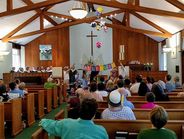 Congregation in the sanctuary for Easter worship: Alleluia with balloons