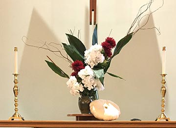 dramatic floral arrangement with coral on the communion table