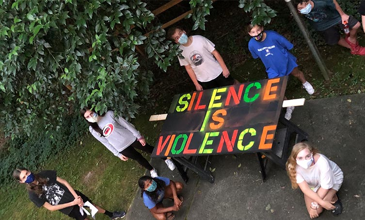 Youth with their Silence is Violence sign for their justice interactive art installation