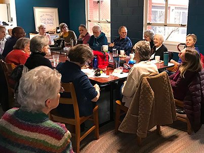 Monday Lunch group gathers around the table for a meal