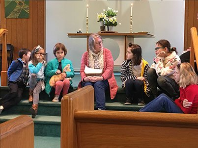 Śānti Matthews and the children sit on the sanctuary steps for Children's Time