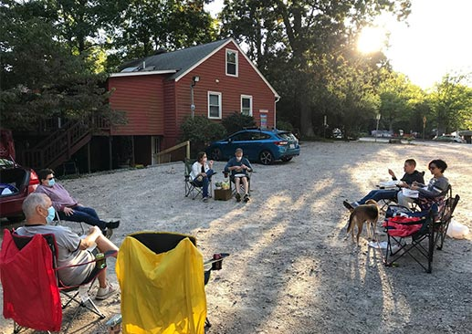 4 families sit in a large, pandemic-appropriate circle for a Tailgate Supper