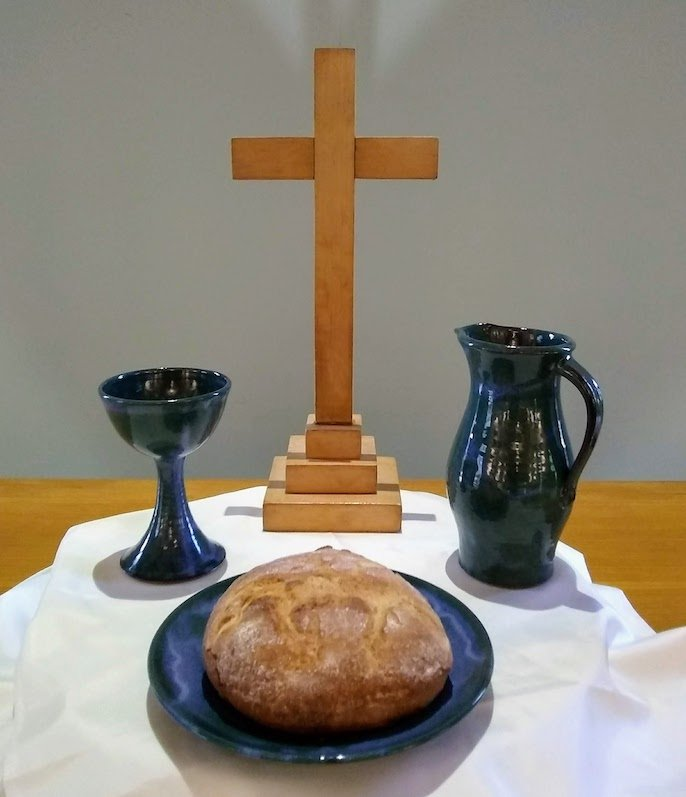 Chalice and pitcher, golden loaf of bread, and a simple wooden cross invite us to this meal of love shared