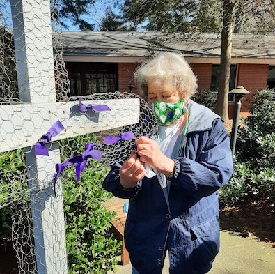 a woman ties her ribbon on the gratitude cross