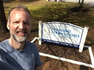 Charles at the Healing Transitions sign